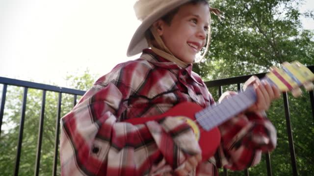 4k little boy dressed in country cloths playing a ukulele - プレイドシャツ点の映像素材/bロール