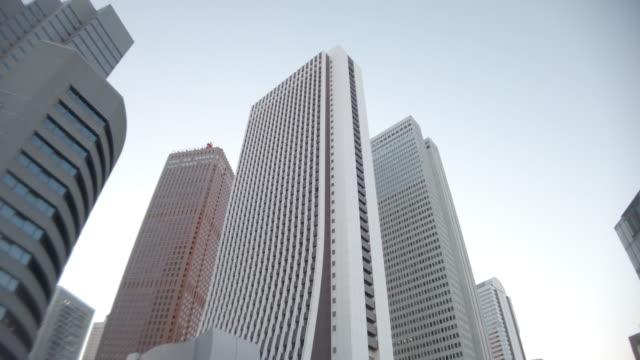 vidéos et rushes de 4k vue d'angle bas , panoramique, tilt up , bâtiment de bureau et ciel à shinjuku - vue en contre plongée