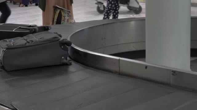 4k: gepäck auf gepäckbandes am flughafen - reisegepäck stock-videos und b-roll-filmmaterial
