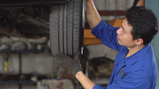 stockvideo's en b-roll-footage met 4k: mannelijke mechanic controleren band in auto reparatiewerkplaats. - east asian ethnicity