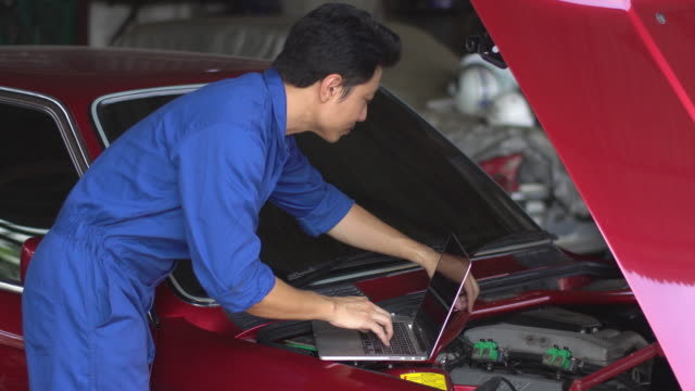 4k: Male using laptop for adjust a car in the garage.
