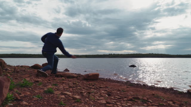 4k man skipping rocks on beautiful lake at sunrise slow motion - stein stock-videos und b-roll-filmmaterial