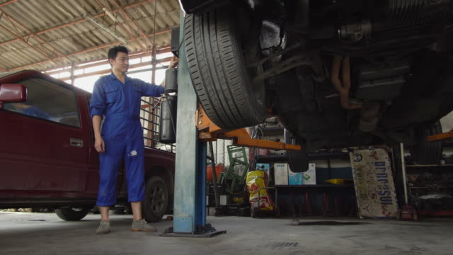 4k: mechanic man using a hydraulic car lift at a automobile repair shop. - hydraulics stock videos and b-roll footage
