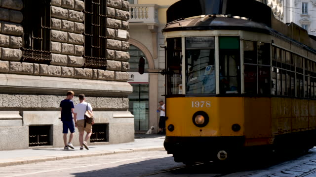 4k milan tram train trolley car. clean, easy and environmentally friendly way for tourists and locals to get around the city. classic vintage looking yellow gold car - environmental conservation stock videos & royalty-free footage