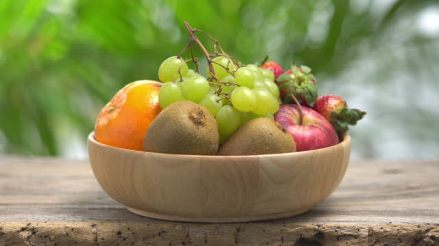 4k mix fruit in wooden bowl with green bokeh background. - fruit bowl stock videos & royalty-free footage