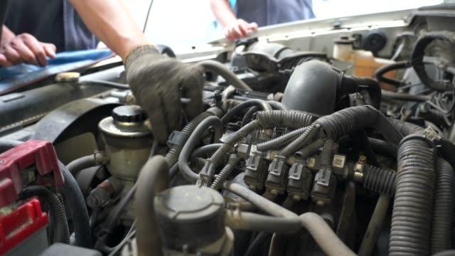vídeos y material grabado en eventos de stock de película de 4 k de mecánico de reparación de un coche viejo. bajo el capó del coche, comprueba el trabajo de carburador y motor - herramienta de mano