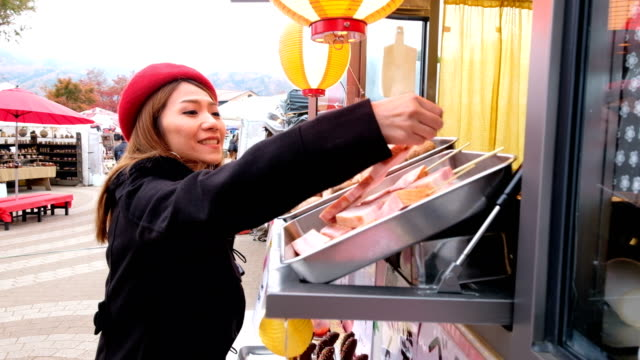 4k moving shot of a asian woman choosing yakitori (grilled pork) from food truck at japan street market - food and drink establishment stock videos & royalty-free footage