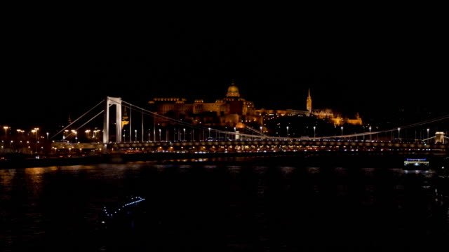 vidéos et rushes de 4k night view of elisabeth bridge and palace and castle behind in budapest hungary. car headlights and traffic can be seen driving across the river and down the waterfront. - pont des chaînes széchenyi