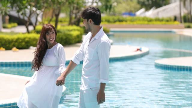 4k i par fritidsresenärer och vandrare njuta av poolen och stranden och lyckliga pensionerade paret på tropiska semester - utebassäng bildbanksvideor och videomaterial från bakom kulisserna