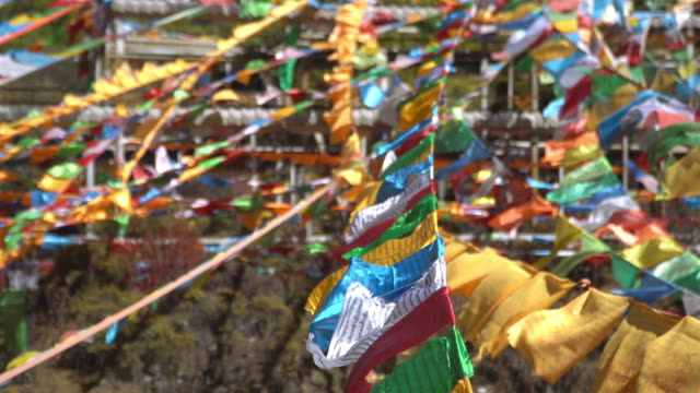 4k of prayer flag blowing wind with lush foliage background. - traditionally tibetan stock videos & royalty-free footage