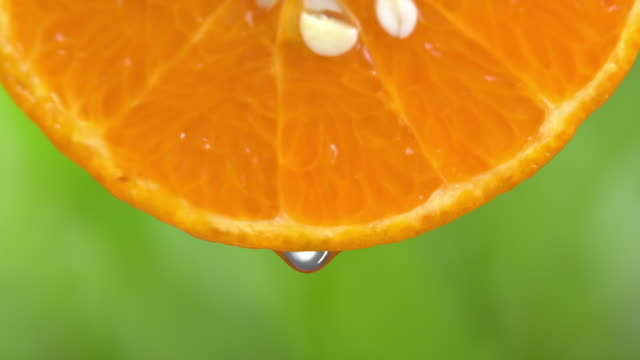 4k of water drop from orange slice. - orange stock videos & royalty-free footage