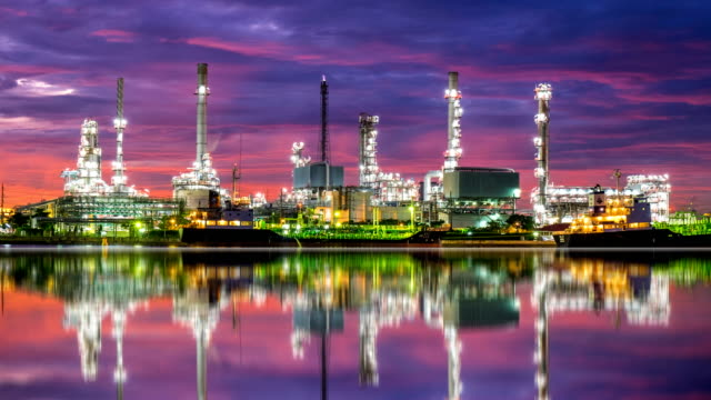 4k oil refinery - petrochemical plant timelapse at sunrise with reflection - industria petrolifera video stock e b–roll