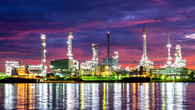 4k Oil refinery - petrochemical plant timelapse at sunrise with reflection
