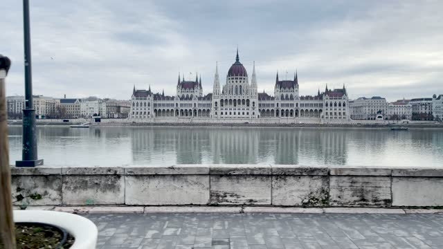 4k panning style budapest parliament building and river danube scene shot through the window of a moving tram along the waterside, hungary - széchenyi chain bridge stock videos & royalty-free footage