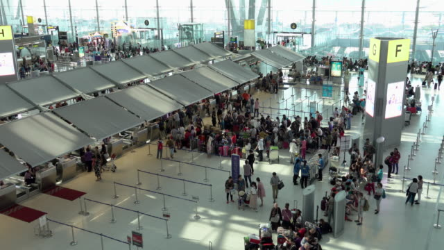 4k: passengers wait at the check in queue in departure terminal of bangkok suvarnabhumi airport - waiting in line stock videos & royalty-free footage