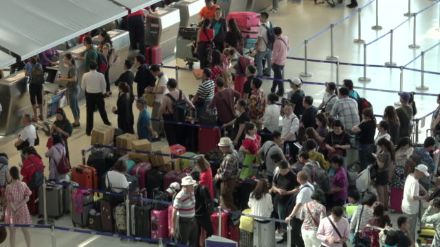 4k: passengers wait at the check in queue in departure terminal of bangkok suvarnabhumi airport - fare la fila video stock e b–roll