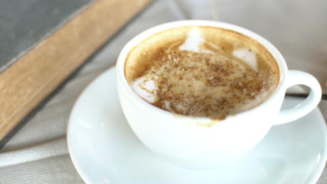 一杯のコーヒーに 4 k 注ぐ砂糖 - カプチーノ点の映像素材/bロール