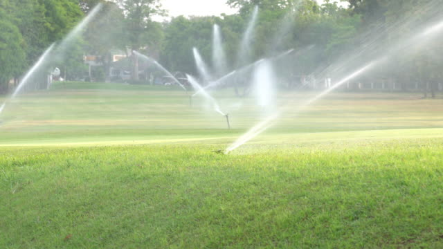 4k real time  sprinkler in park - irrigation equipment stock videos & royalty-free footage