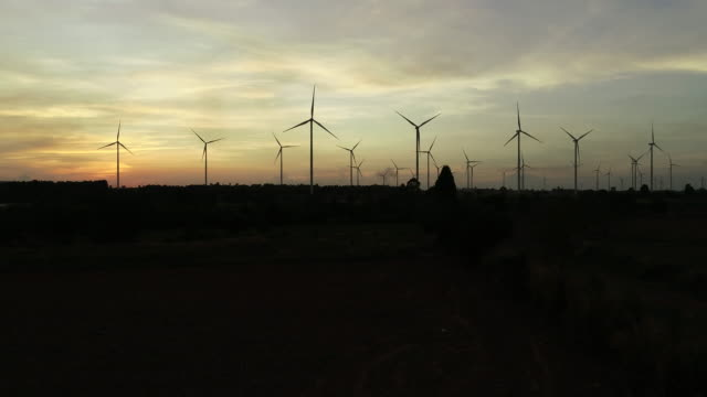 4k resolution aerial shot by drone wind turbine natural energy at twilight - turbine stock videos & royalty-free footage