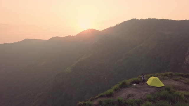 4k resolution aerial view of tourist photographer camping and tent over the cliff and beautiful mountain,travel adventure concept at  phu tubberk thailand - cliff stock videos & royalty-free footage