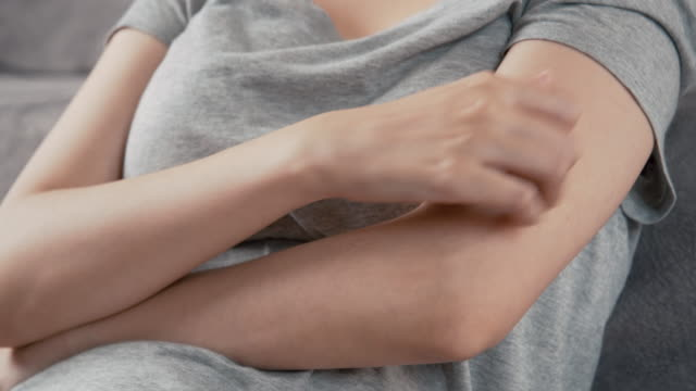 4k resolution asian woman scratching on her arm while working at home office. - dry stock videos & royalty-free footage