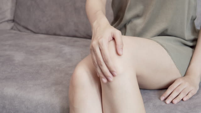 vídeos de stock e filmes b-roll de 4k resolution asian woman sitting on a couch having a knee pain and she massage on her knee - dor