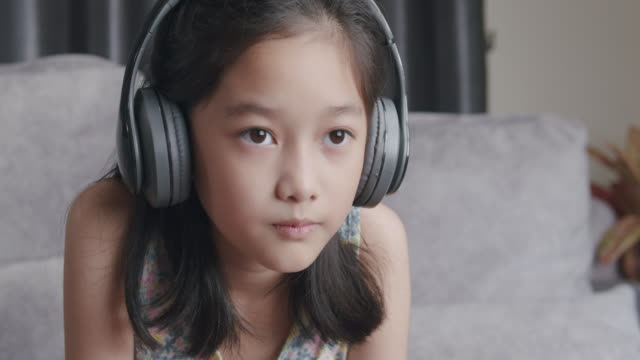 4k resolution attractive asian girl wearing wireless headphone sitting and playing online video game console at home. kid enjoy to play a game while stay at home with coronavirus lockdown situation - sister stock videos & royalty-free footage