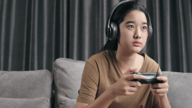 4k resolution attractive asian girl wearing wireless headphone holding joystick or game controller and playing online video game console at home. kid upset or anger to play a game while stay at home with coronavirus lockdown situation - loss stock videos & royalty-free footage