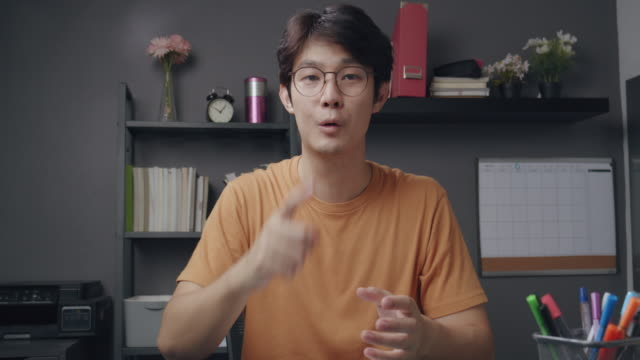 4k resolution attractive asian man teacher explaining math homework to his online student on video conference. he using online video call technology teaching mathematical formula from home while coronavirus lockdown. telecommuting and online learning. - teacher stock videos & royalty-free footage