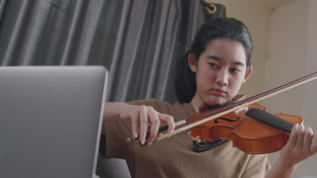 4k resolution attractive asian teen girl practice and learning violin online lesson with her teacher by using laptop computer while stay at home from coronavirus lockdown situation.young woman playing classical music instrument. - violin stock videos & royalty-free footage