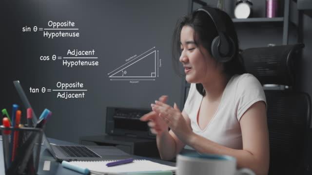 vídeos y material grabado en eventos de stock de 4k resolución atractiva chica adolescente asiática explicando la tarea de matemáticas a sus amigos a través de la computadora portátil. enseñanza en línea de fórmula matemática desde casa, mientras que coronavirus lockdown. conceptos de teletrabaj - clase de formación