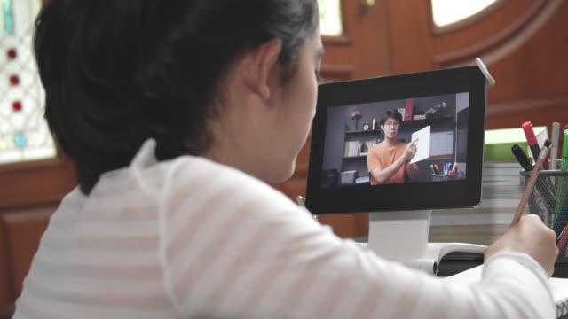 コロナウイルスや居心地の良い19ロックダウン状況ながら、オンラインホームスクールでタブレット画面上で彼女の教師eラーニングで勉強する4k解像度魅力的なアジアのティーンエイジャー� - remote location点の映像素材/bロール