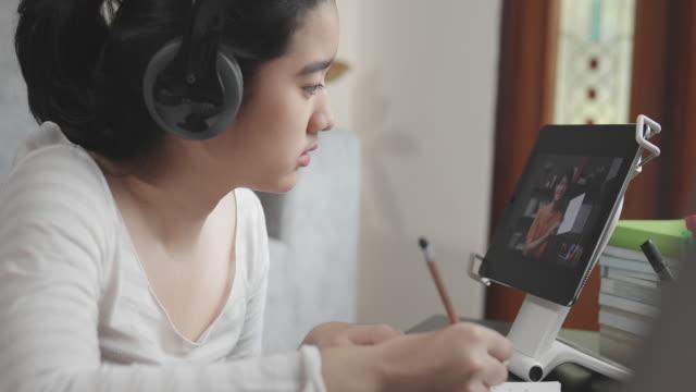 stockvideo's en b-roll-footage met 4k resolutie aantrekkelijke aziatische tiener meisje dragen hoofdtelefoon en studeren met haar leraar e-learning op tablet scherm met online homeschool, terwijl coronavirus of covid 19 lockdown situatie. video gesprek technologie met haar advies om haar hu - e learning
