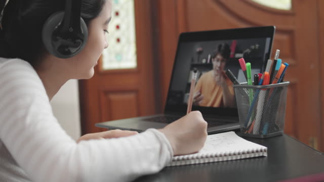 4k resolution attractive asian teenager girl wearing headphone  and studying with her teacher e-learning on tablet screen with online homeschool while coronavirus or covid 19 lockdown situation. video call technology with her advice to learn her homework. - university student stock videos & royalty-free footage