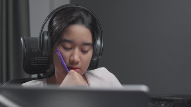 vidéos et rushes de 4k résolution attrayante fille adolescente asiatique portant un casque et étudiant avec son professeur e-learning sur l'écran tablette avec homeschool en ligne tandis que le coronavirus ou covid 19 situation de verrouillage. technologie d'appel vid� - niveau collège lycée