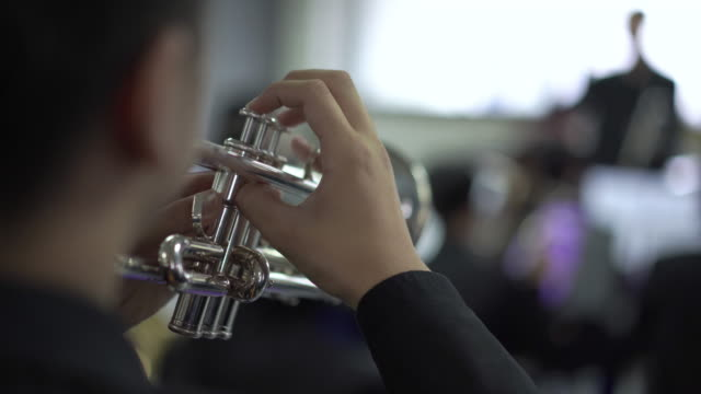 4k resolution close up hand of trumpet section in wind band - trumpet stock videos and b-roll footage