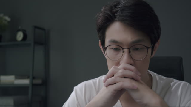 4k resolution close-up shot attractive asian man looking on laptop computer and feel depression or worry on his work and financial problem while sitting in home office. lockdown situation from coronavirus or covid 19. - east asian ethnicity stock videos & royalty-free footage