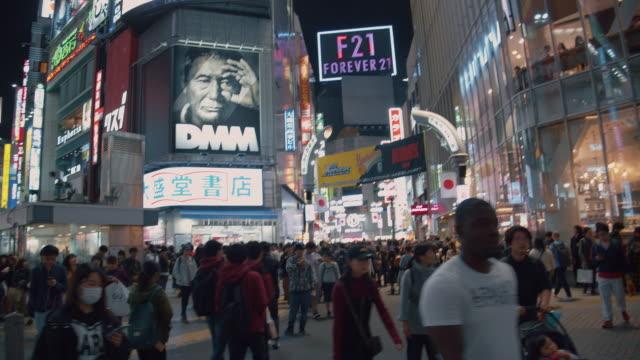 4k auflösung kräht von menschen nachtleben an shibuya kreuzung. verkehrsauto und transport über kreuzung - wegweiser stock-videos und b-roll-filmmaterial