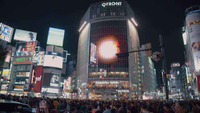 4k resolution crowed of people night life at shibuya crossing. traffic car and transportation across intersection - commercial sign stock videos & royalty-free footage
