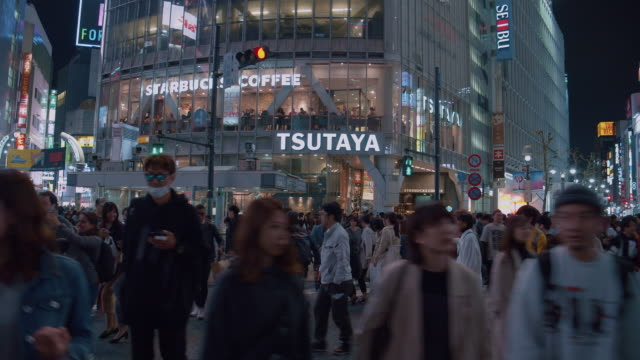 stockvideo's en b-roll-footage met 4k resolutie kraaide van mensen nachtleven bij shibuya crossing. verkeer auto en transport over kruispunten - shibuya shibuya station