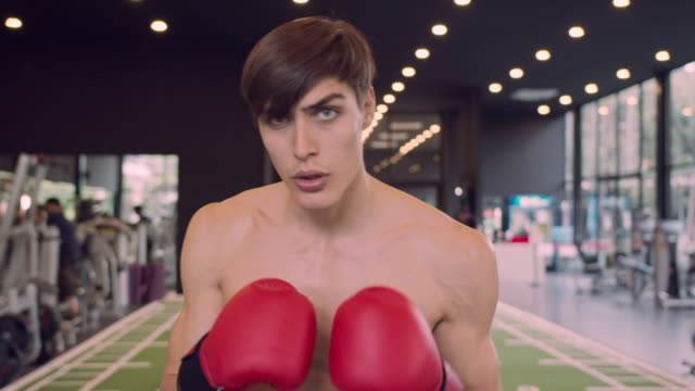 ジムでカメラにパンチを練習4k解像度ハンサムな男ボクサー - ボクシンググローブ点の映像素材/bロール