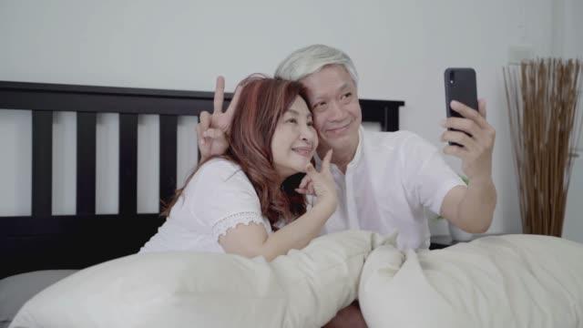 4k auflösung happy asian senior couple senior carice technologie-gerätekonzept, lovely älteren paar nehmen ein selfie mit von ihnen smartphone - weitere themen stock-videos und b-roll-filmmaterial