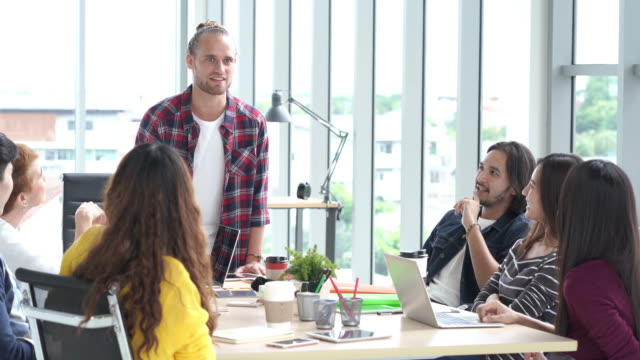 4k resolution multi ethnic creative team brainstorming in smart casual wear having a meeting while standing at modern office - coworking space stock videos and b-roll footage