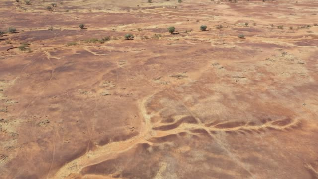4k resolution of a moving video over red and orange earth and dry water channels outback australia - 絶滅点の映像素材/bロール