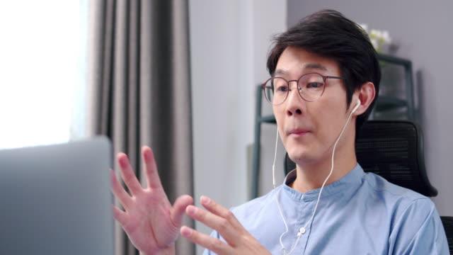 vidéos et rushes de résolution 4k de l'homme asiatique attrayant portant des écouteurs ayant la vidéoconférence ou l'appel vidéo par ordinateur portable avec son partenariat tout en travaillant de la maison avec coronavirus ou covid 10 situation. - webinaire