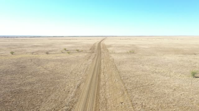 4k resolution of drone footage over red and orange earth,dry water channels, a road and blue sky, outback australia - outback stock videos & royalty-free footage