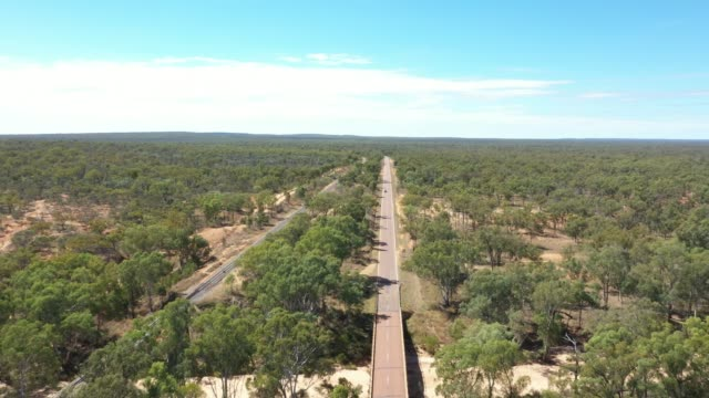 4k resolution of drone footage over red and orange earth,dry water channels, a road and blue sky, outback australia - cultures stock videos & royalty-free footage