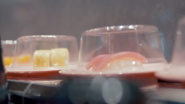 4k resolution of sushi on a rail in sushi restaurant. - toro fish stock videos and b-roll footage