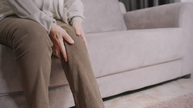 vídeos de stock, filmes e b-roll de resolução 4k mulher asiática sênior usando a mão massageando em sua dor na perna.conceito de cuidados de saúde.close-up shot. - dor