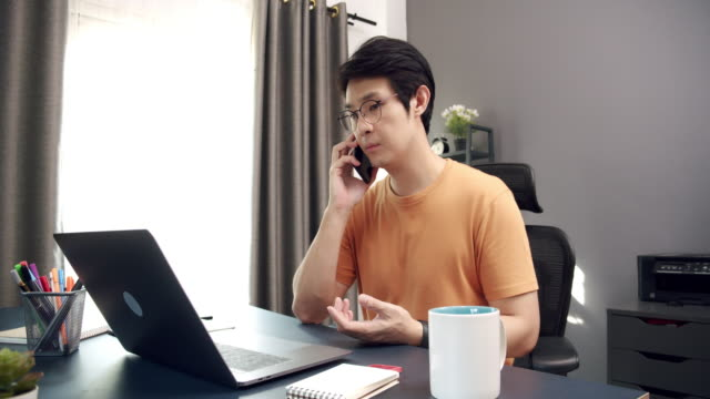 vídeos de stock e filmes b-roll de 4k resolution slow motion of attractive asian adult man talking with his partner on the smartphone while using laptop computer in home office  while work from home from quarantine coronavirus or covid 19 situation - sudeste asiático